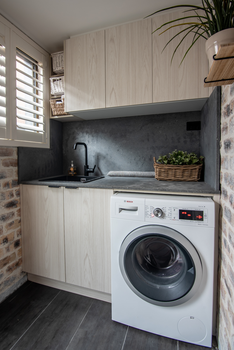 Laundry featuring exposed brick