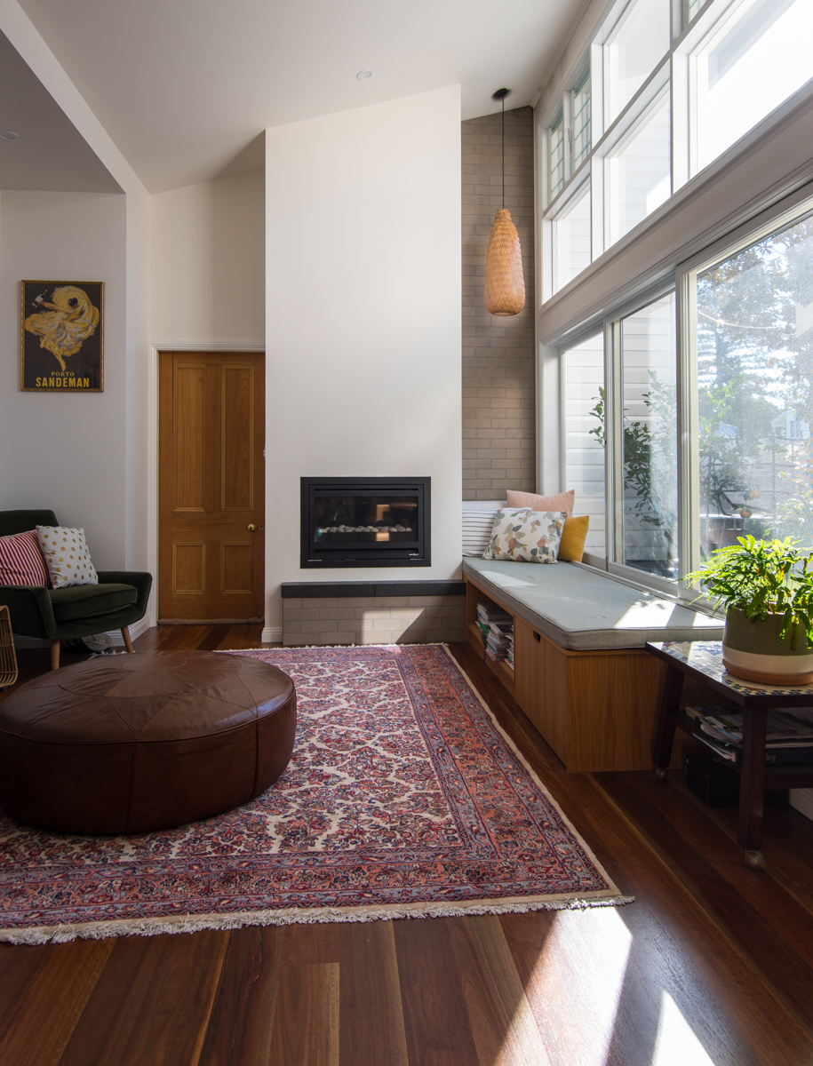 Lounge room with glazed wall, fire place & built-in seat